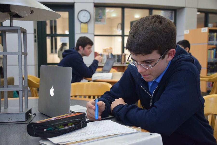 Bergman intently focuses on finishing his math homework.