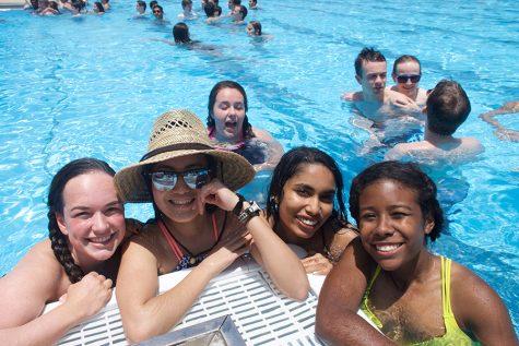 Caroline White, Allice Park, Devina Naidu, and Jarelis Cabrera relaxing poolside