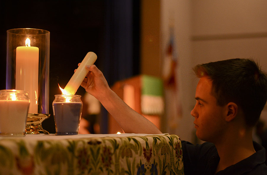Junior Matthew Castro lights a candle for each human trafficking survivor story heard by the students during the Peace Jam chapel. There were six candles that were lit, representing the six survivors and their stories.