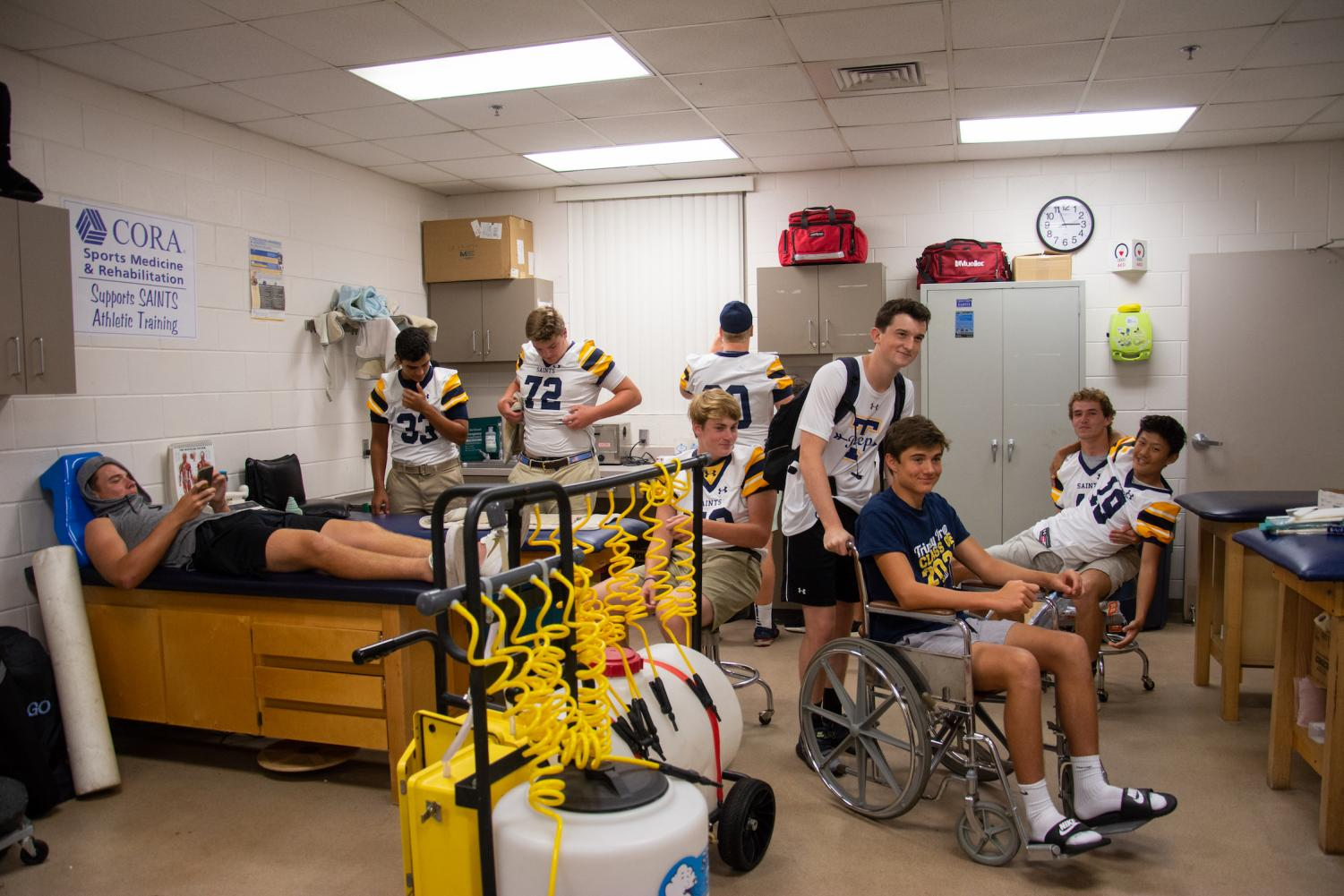 Members of the varsity football team hang out in the training room pregame.