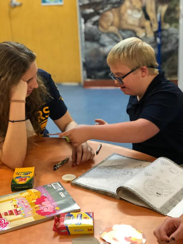 Senior Leah Mauer assists a student from UCP Bales in coloring. Mauer is one of twenty students who participates in Best Buddies.