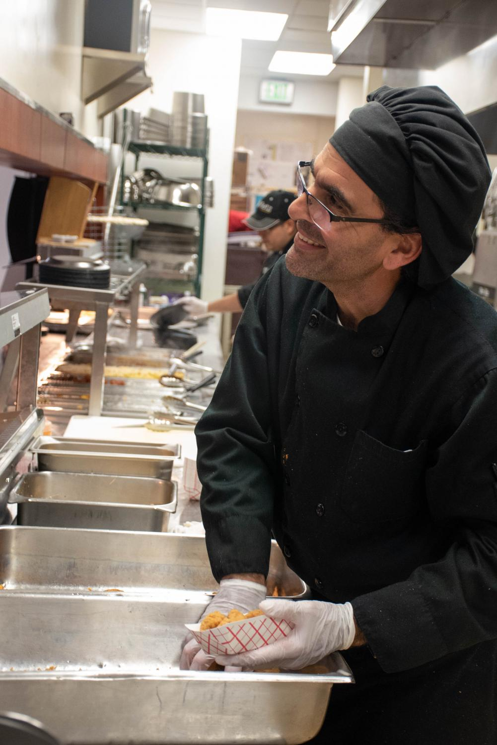 Chris serves up chicken tenders and smiles to students in the Grille during Upper School lunch. He said he appreciates the students and their friendly nature.