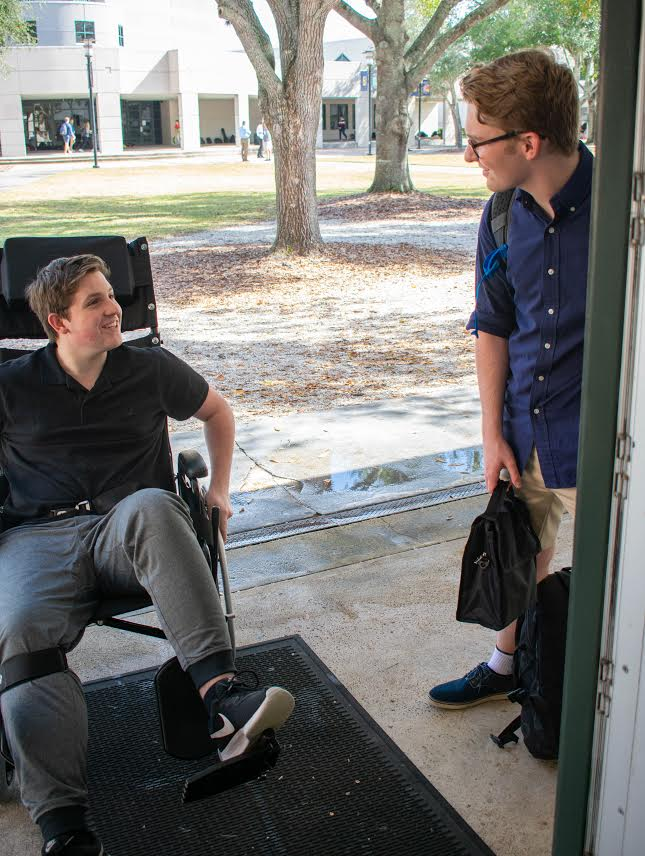 Sophomore+Thomas+Lightsey+rolls+his+wheelchair+into+his+English+class+as+senior+Robby+Witten+holds+the+door.+Lightsey+says+that+his+friends+are+more+than+willing+to+hold+open+doors+and+push+him+around+campus+since+his+surgery+in+December.++
