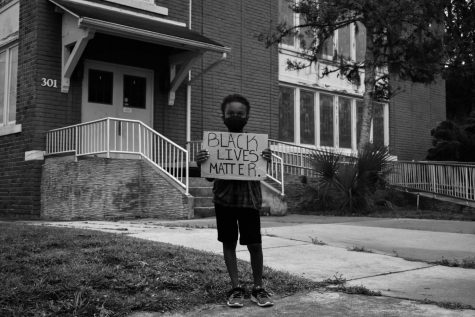 Adrian Beaupierre, a Sanford raised child, holds a sign supporting the Black Lives Matter movement. This movement impacts people of all ages, genders, and races in the fight for systematic equality.