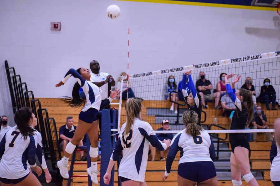 Freshman Victoria Hill spikes the ball at the opposing team during a game with many more fans due to the loosened rules. On Sept. 8. Trinity Prep beat the Masters Academy with a score of 3-0.