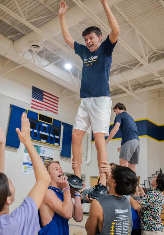 Junior Carlos O'Connor practices flying for the group dance with his stunt group, taught by junior cheerleader, Anna Miliotes.