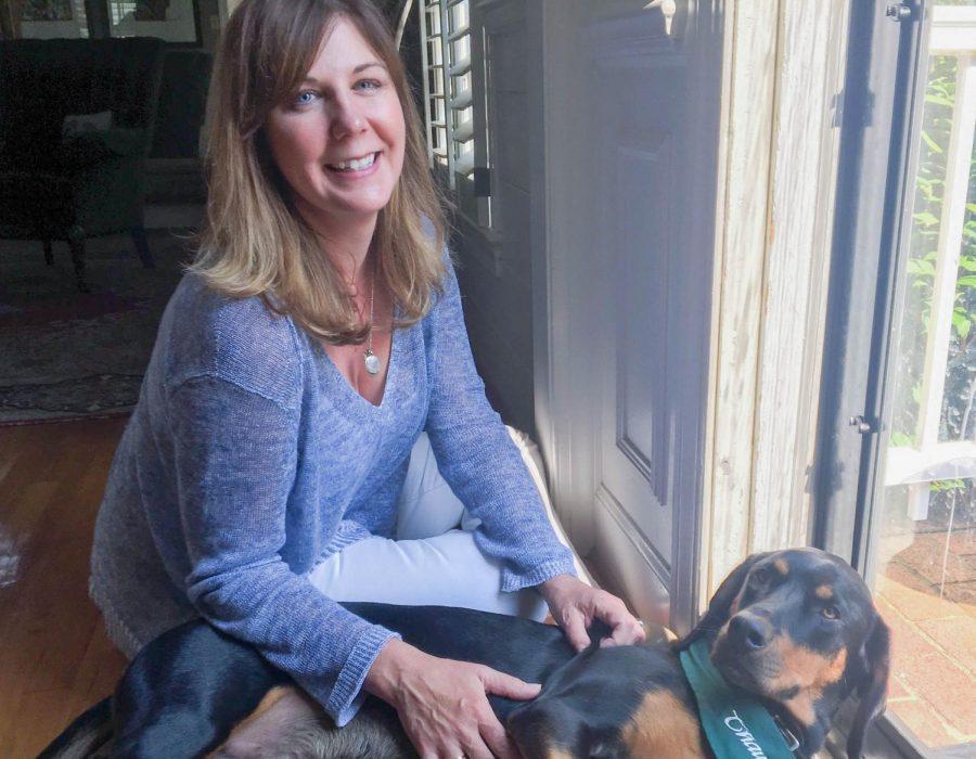 Librarian Lee De Groft pets her black and tan coonhound Brodie.